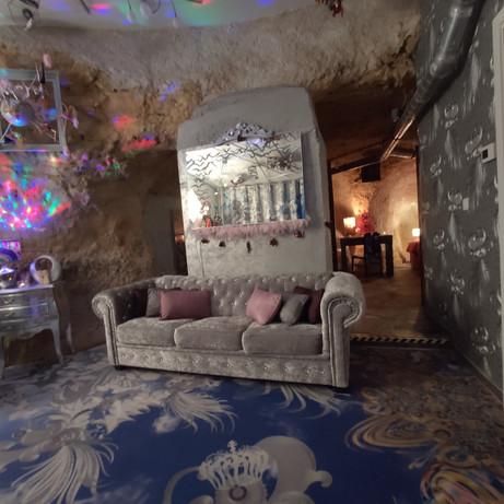 Le salon du Loft coté chesterfield on voit l'entrée de la chambre de part et d'autre et de l'autre coté on trouve la baie vitrée donnant sur le grand jardin