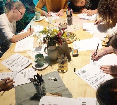 Workshopsituation: Ein Tisch, an dem geschrieben und gezeichnet wird.