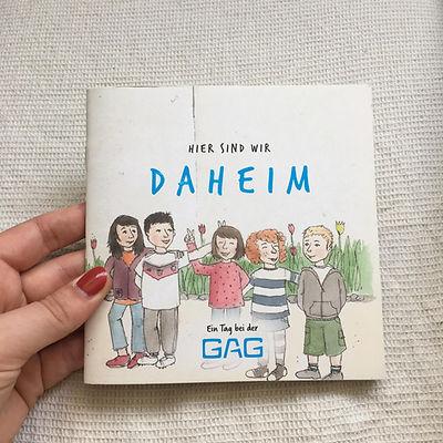 """Das Kinderbuch """"Hier sind wir daheim"""". Es zeigt fünf Kinder, die lachend den Arm umeinander legen"""