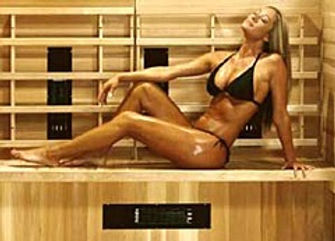 Sexy lady wearing black bikini in infrared sauna at Dangerous Curves