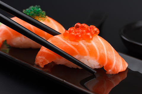Salmon sushi nigiri in chopsticks over b
