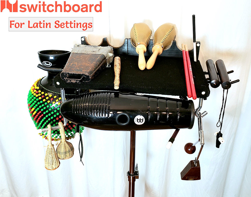 Switchboard for Latin settings - LEFT: shekere hung from 2 Fat hooks; TOP: campana & beater, rawhide maracas (in divots), timbale sticks, guiro scraper (in corner hole); RIGHT: claves and samba whistle on 2 Skinny hooks; BOTTOM: caxixi on L-hook, guiro on 2 L-hooks, and vibraslap on J-hook