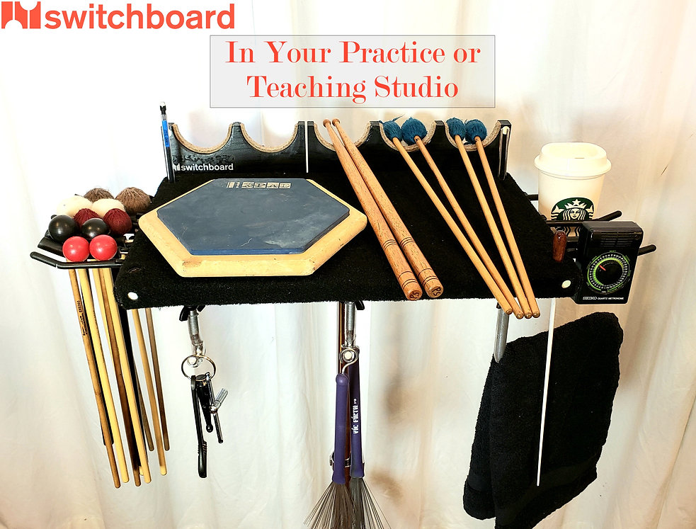 "Switchboard in the Practice/Teaching Studio -Left: xylo, rubber, vibe, timp, and soft marimba mallets; Top: mechanical pencil, tuning fork, and conducting baton in corner holes, 6"" pad, 1 pair SD sticks and 2 pairs of marimba mallets (each in their own divot); Right: Your favorite beverage and a metronome; Bottom: drum key/wrench, wire brushes, and extra towel. All mounted via 10 switchhooks, 2 J-hooks, and 1 L-hook"