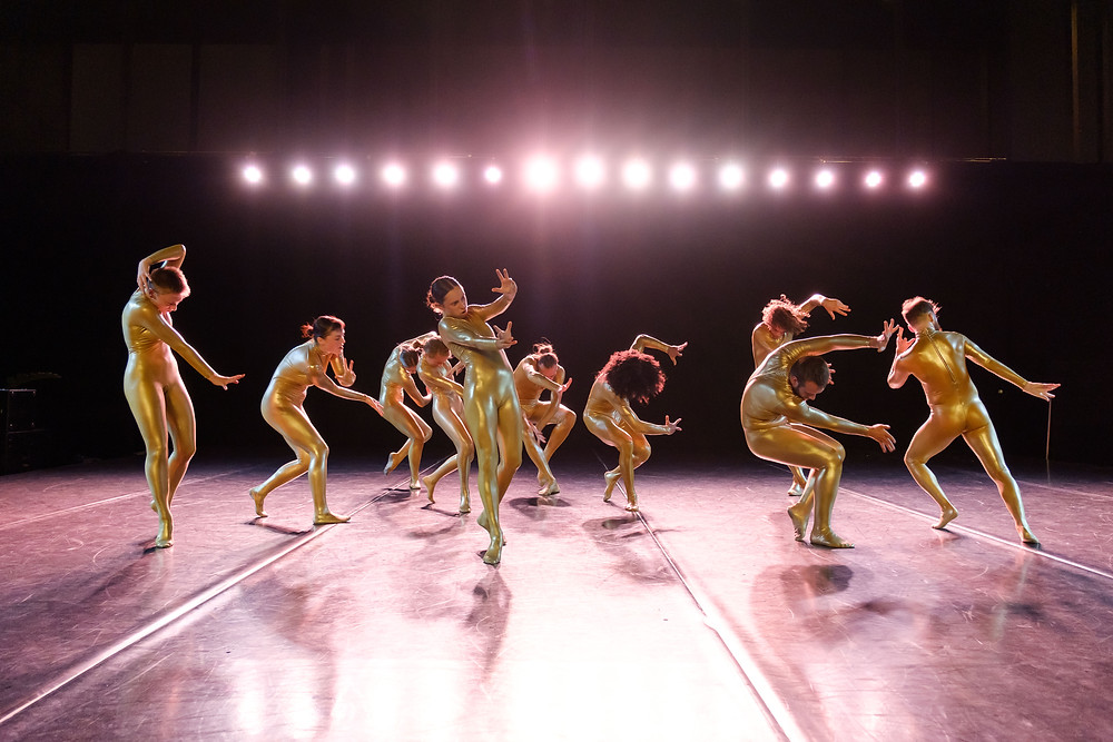 Contemporary dancers in skintight gold body suits on a dance floor underneath pink spotlights