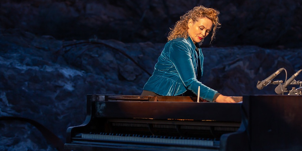 Gabriella Smart in a blue velvet jacket standing at the side of a grand piano, playing from within side