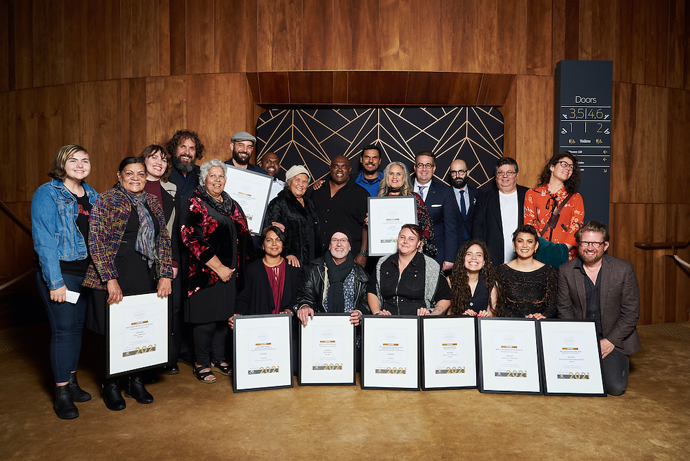 Hecate & Yirra Yaakin team holding awards against the wooden wall panelling at the State Theatre Centre of WA