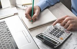 man-hand-using-calculator-and-writing-ma