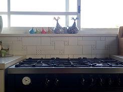 חיפוי מיוחד בשמנת ודוגמאות עדינות מעל תנור משולב במטבח ביפעת