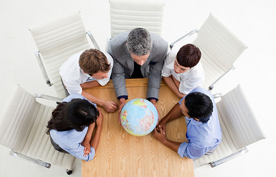 People sitting around a table with a globe on it
