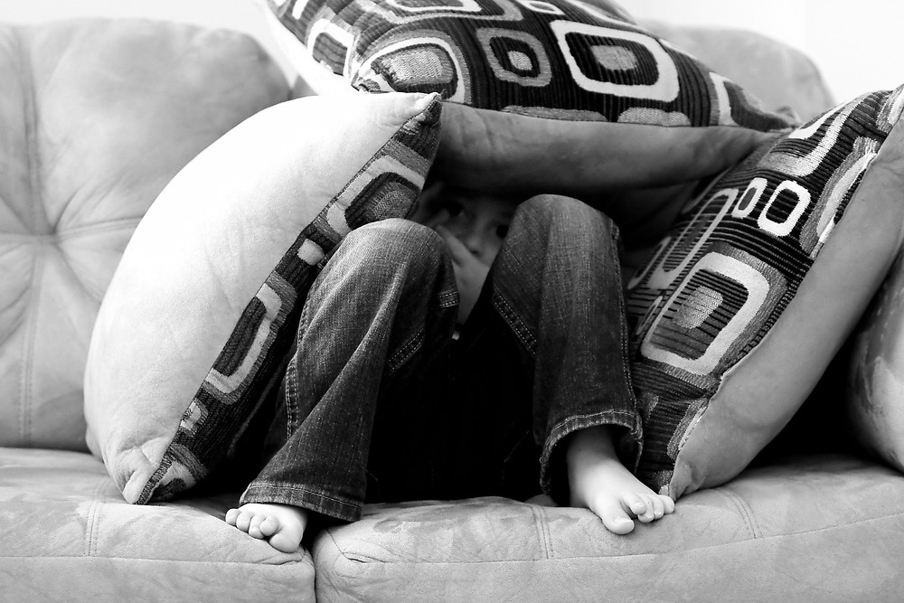 ילד מתחבא בין כריות כתגובה לחרדה