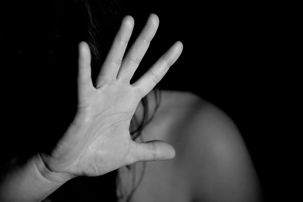 אישה המתגוננת ע״י הרמת כף היד מול הפנים