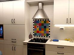נקודת פוקוס צבעונית מעל הכיריים בין אריחים לבנים במטבח בירושלים