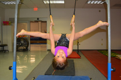 girl upside down straddle on rings