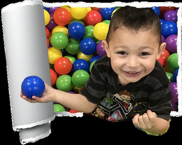 little boy enjoying the ball pit
