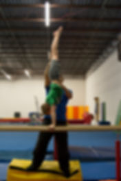 boy doing handstands on parallel bars