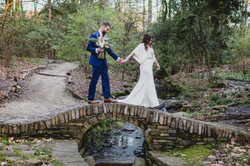 Bride and groom walk across bridge while holding hands at UNCC Botanical Gardens