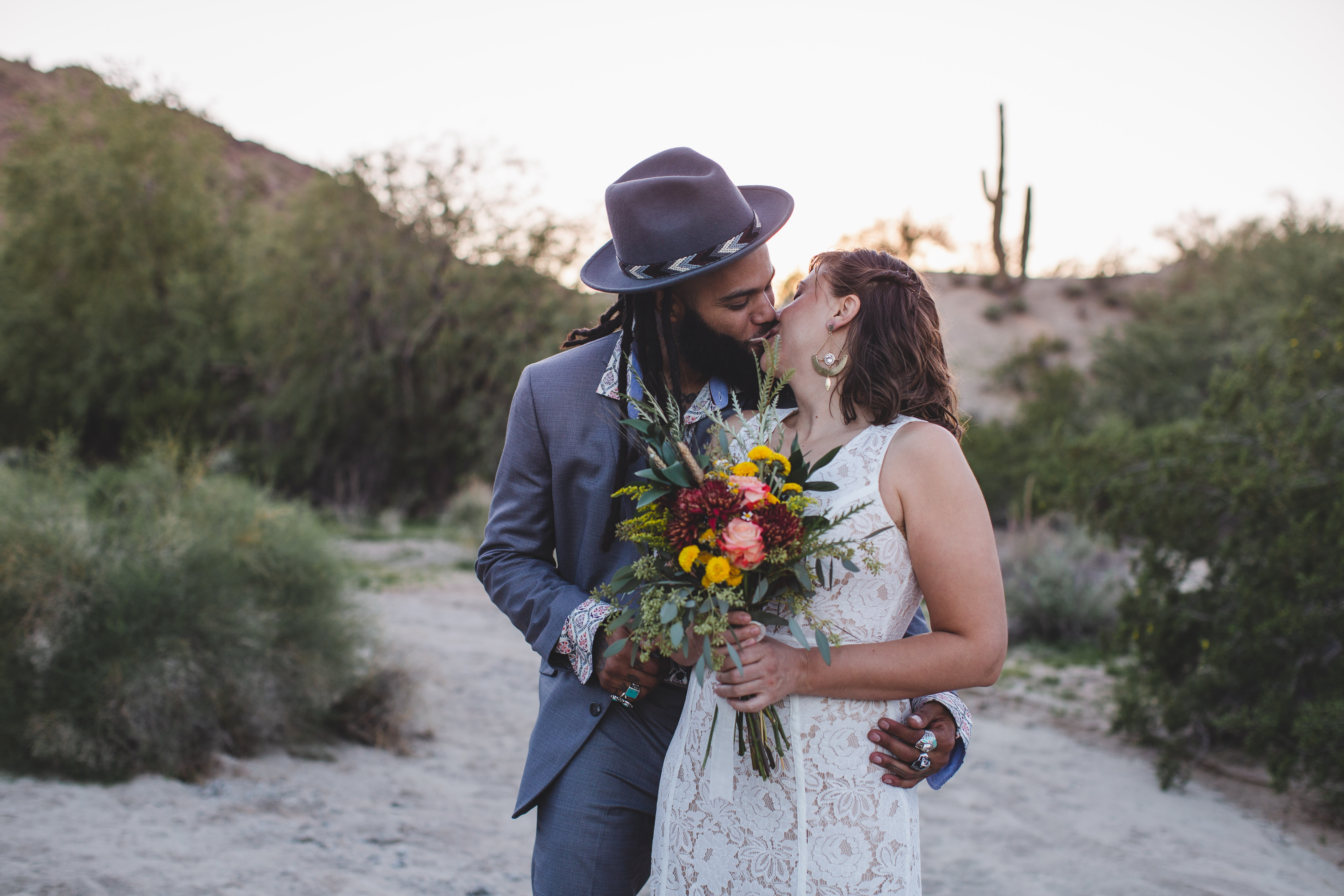 Bride and groom kiss during desert adventure elopement