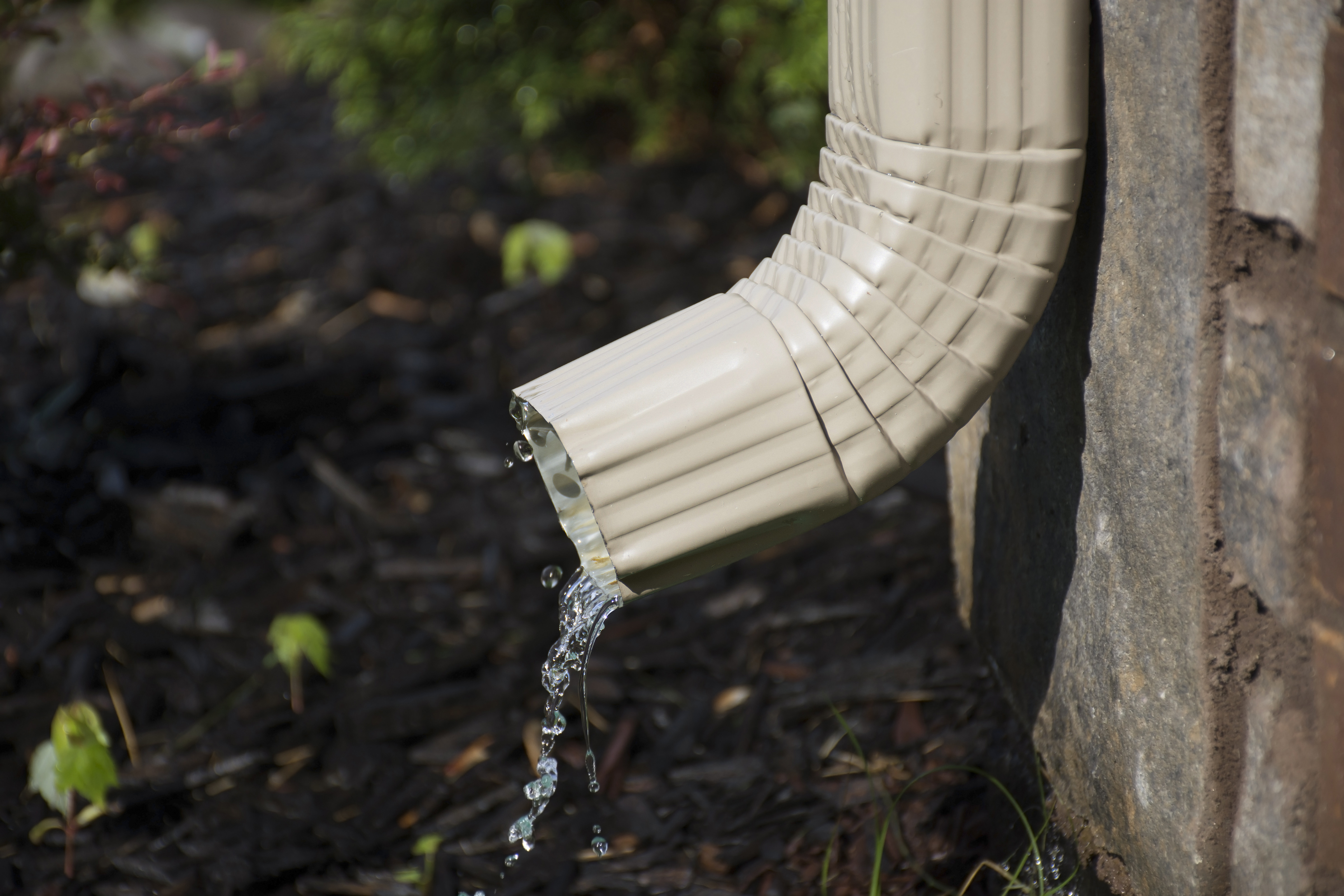 A rain gutter downspout with water comin