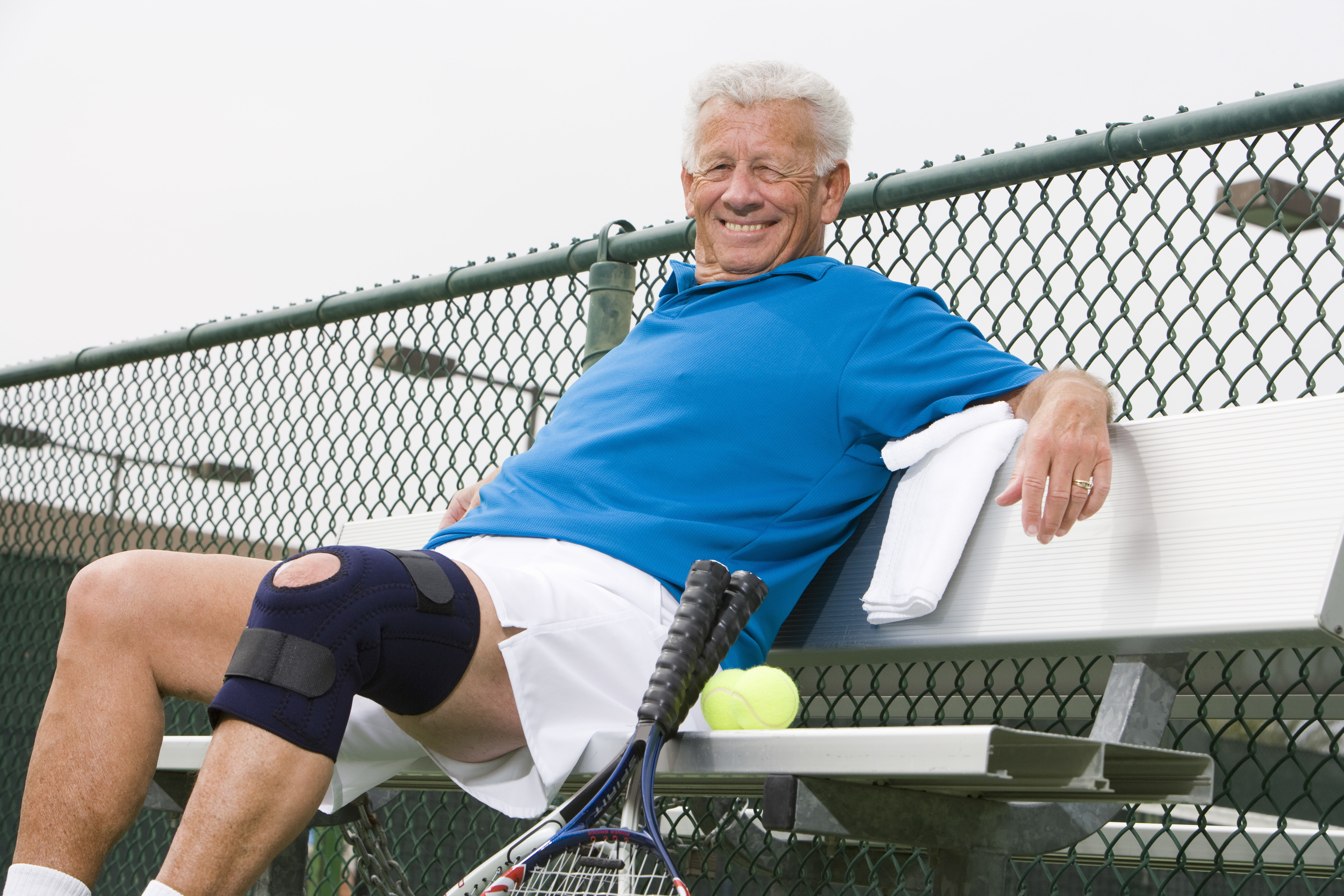 senior-tennis-player-relaxing-on-bench-29652389