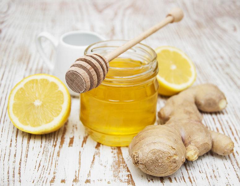 honey,  lemon and ginger on a wooden bac