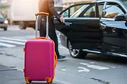 Orlando Limo Chauffeur closing car door and pink suitcase outside