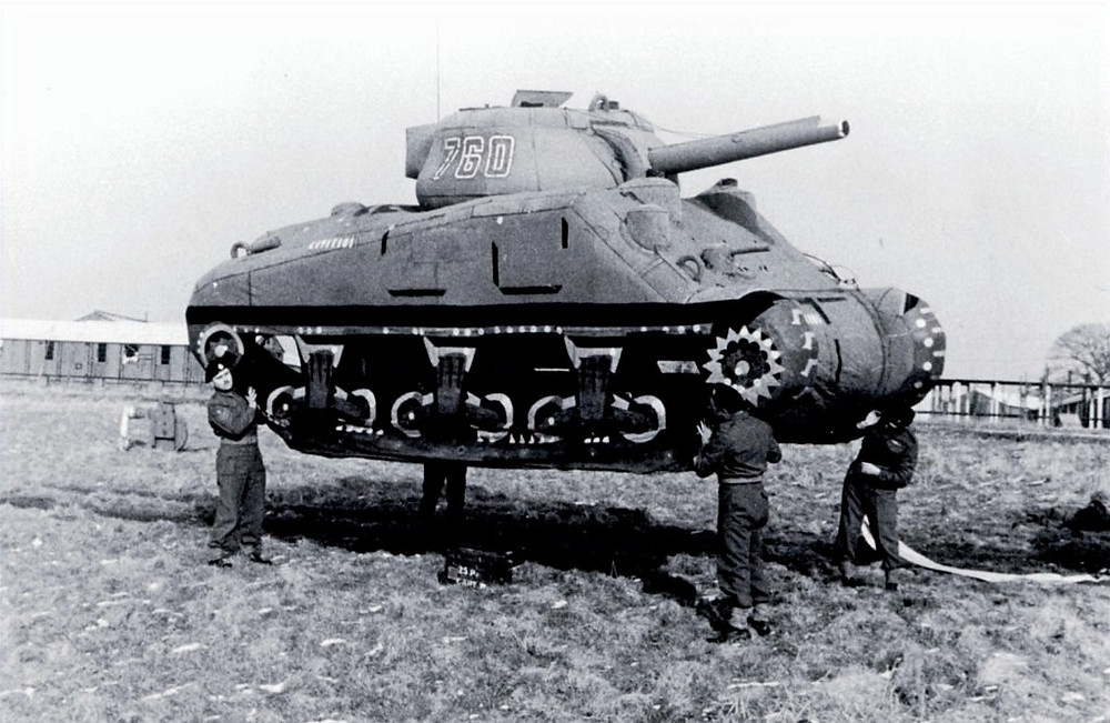 A world war 2 Inflatable tank being held by soldiers