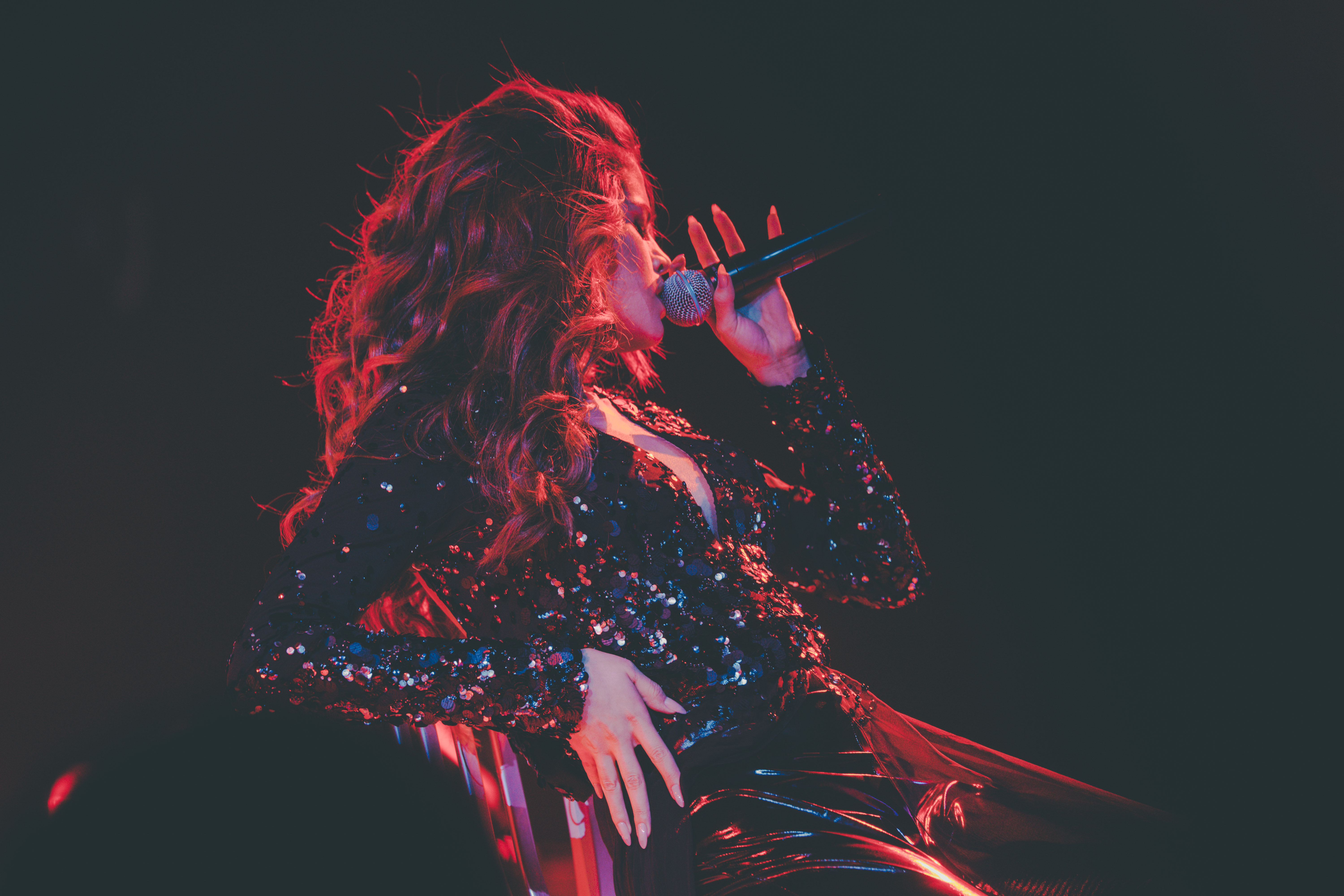 Selena Gomez performing during her Revival Tour in red lighting by Izak Rappaport