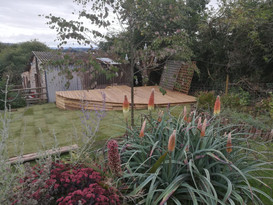 Raised decking area on sloped grass in half tear shape