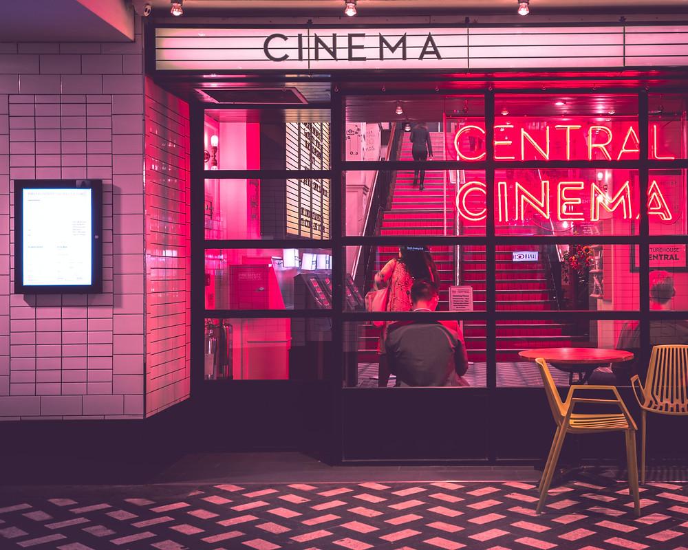 """Der Eingang eines Kinos mit roten Leuchtbuchstaben, die sagen """"Central Cinema"""""""