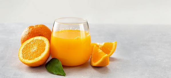 Fresh orange juice glass and oranges on light background_2x.png
