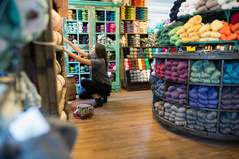 Woman in knit store to demonstrate working on content marketing as part of marketing strategy