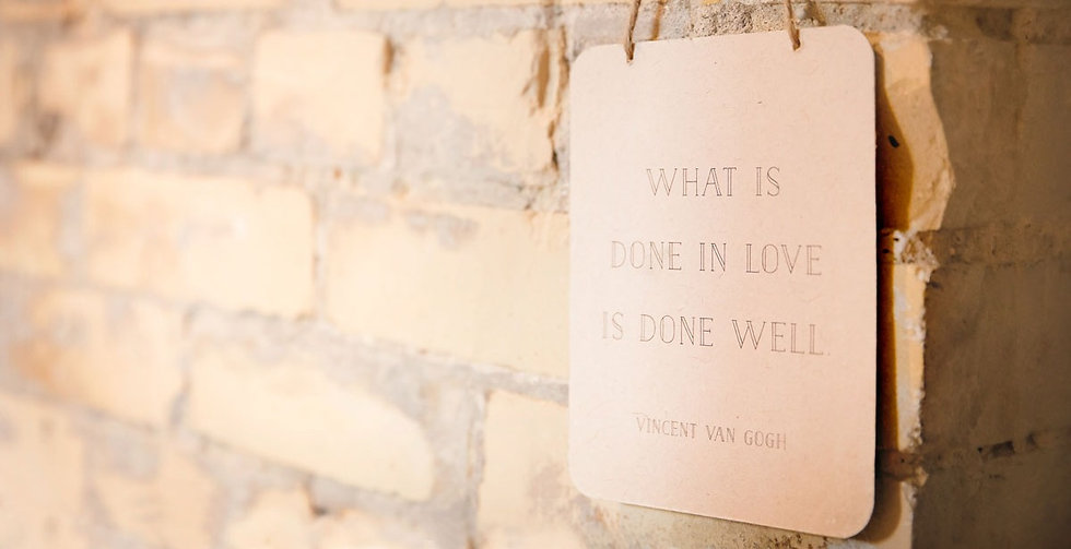 Sign on a brick wall with a quote attributed to Vincent Van Gogh, What is done in love, is done well.