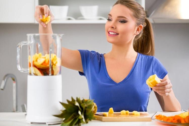 Mulher jovem fazendo uma vitamina de frutas antioxidantes para prevenir o envelhecimento da pele