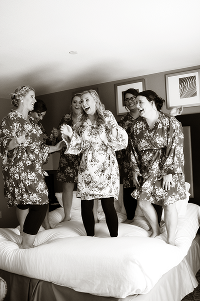 Bridesmaids jumping on bed at East Peoria hotel