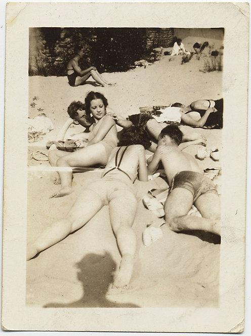 SHADOW of PHOTOGRAPHER BETWEEN WOMAN'S LEGS LYING on BEACH