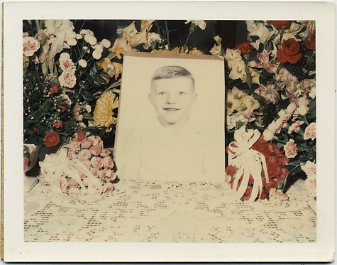 IN MEMORIAM? POLAROID PORTRAIT of YOUNG BOY against BANK of FLOWERS