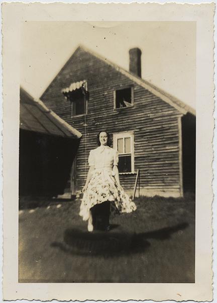 fp6520(WomanInApron_StandingInTire_House)