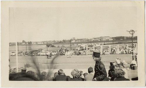 DRUM MAJORETTE PASSES by GRANDSTAND at FAIRGROUND HORSE RACE TRACK