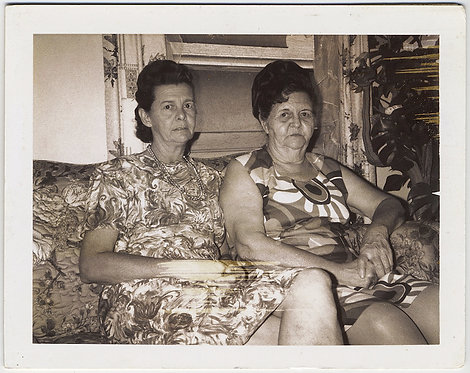 POLAROID UNHAPPY DOUR WOMEN in PATTERNED DRESSES TOGETHER on FLORAL COUCH