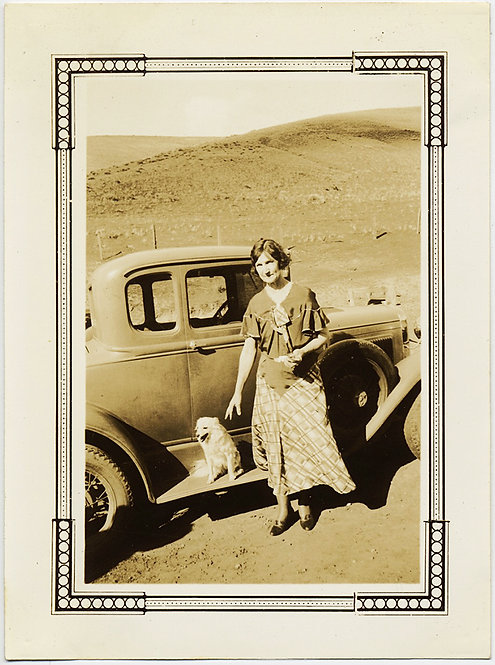 WOMAN by VINTAGE CAR in DESERT LANDSCAPE with WHITE DOG on RUNNING BOARD