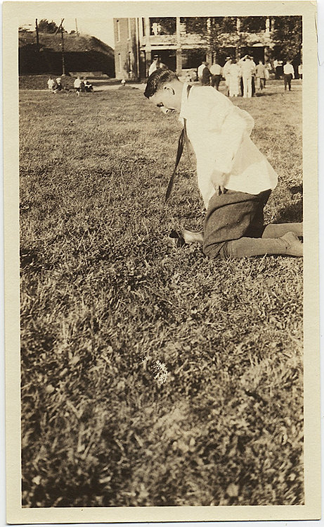 SHOELESS MAN KNEELS on GRASS TIE FLAPPING UNUSUAL