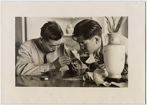 TWO FOCUSED ASIAN MEN  WORK DILIGENTLY on FINELY MACHINED OBJECT