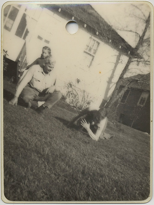 STRANGE LAMINATED SNAPSHOT FAMILY PLAYS with PUPPY on SUBURBAN LAWN
