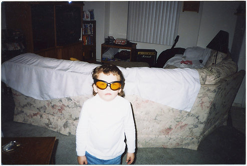 BOY with FRWAKY ORANGE GOGGLES in DOMESTIC INTERIOR!  Weird!