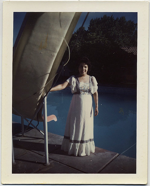 POLAROID WOMAN in INAPPROPRIATELY LONG FRILLY DRESS STANDS by POOL & WATER SLIDE