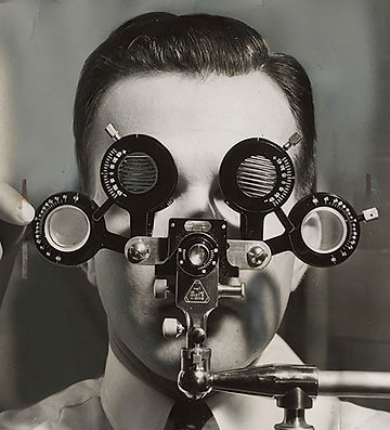 man looking through optometrist's measuring tool