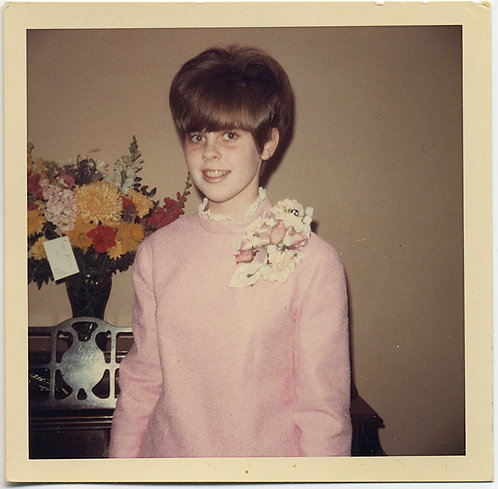 BANGS BEEHIVE BAGS under EYES and a BIG CORSAGE on YOUNG PIANISTS PINK DRESS