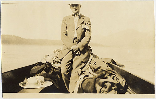 DAPPER MAN SITS on PILES of CLOTHING at PROW of ROWBOAT
