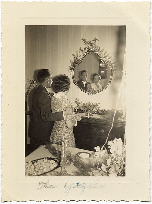 HOMELY COUPLE ADMIRE REFLECTION of SELVES in GILDED ORNATE MIRROR BACK to CAMERA