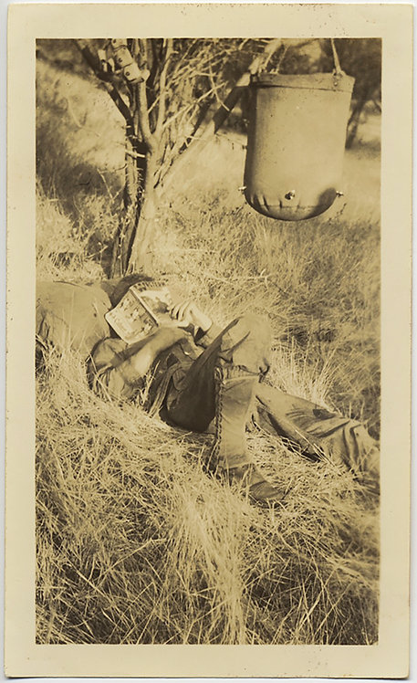 SLEEPING SOLDIER READS COMIC BOOK in GRASS w PORTABLE WATER TANK SUSPENDED